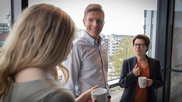 Three people standing in office drinking coffee. Photo.