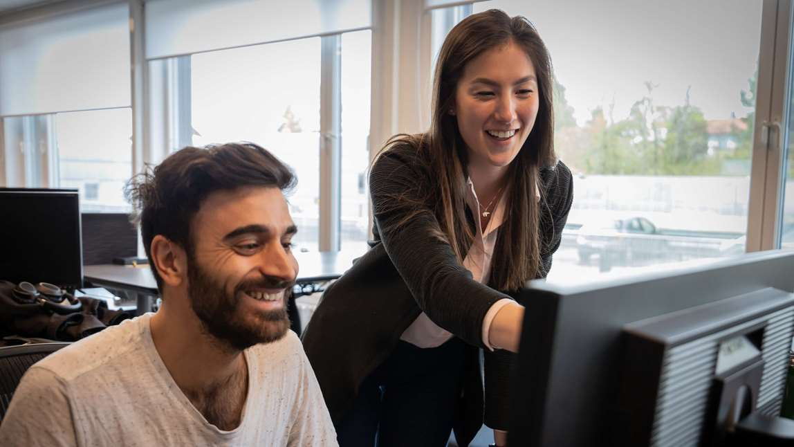 Two people watching a computer screen and smiling. Photo.