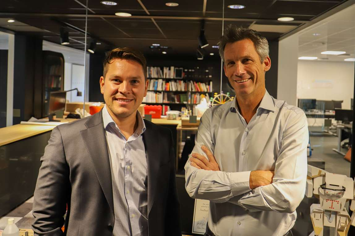 Two men posing in meeting room. Photo.