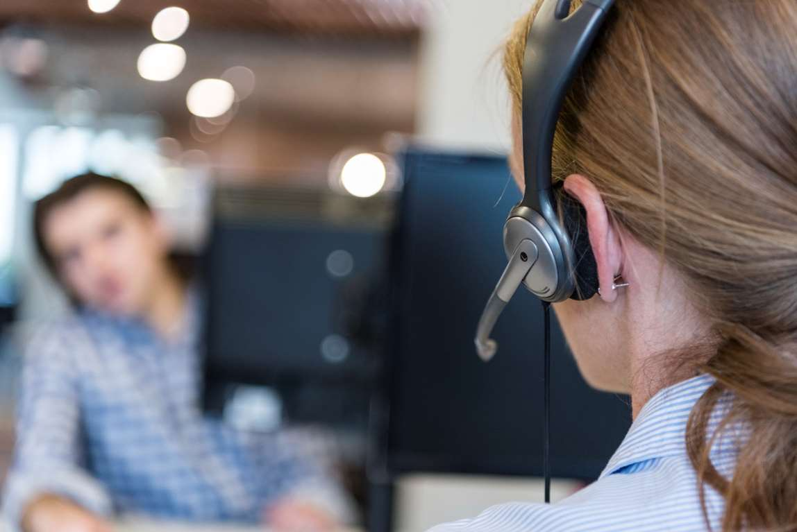 Person talking in handsfree telephone in call center. Photo.